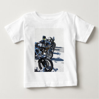 Motorcycles parked in row on asphalt baby T-Shirt