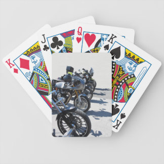 Motorcycles parked in row on asphalt bicycle playing cards