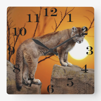 Mountain lion at sunset square wall clock