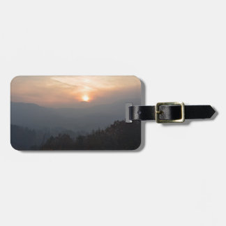 mountain sunset in a haze luggage tag