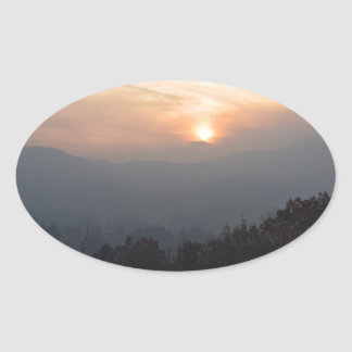 mountain sunset in a haze oval sticker
