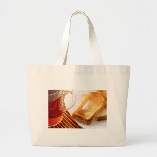 Mug of tea and hot toast with butter large tote bag