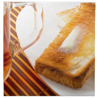 Mug of tea and hot toast with butter napkin