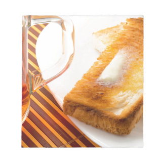 Mug of tea and hot toast with butter notepad