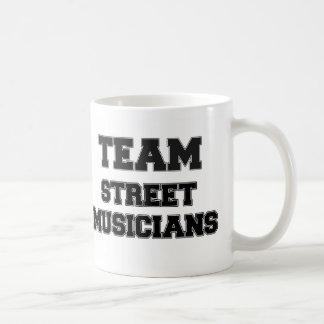 Musiciens de rue d'équipe tasse