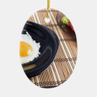 Natural homemade breakfast of fried egg and salad ceramic oval ornament