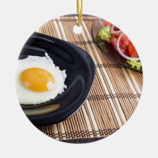 Natural homemade breakfast of fried egg and salad round ceramic ornament