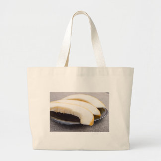 Natural pieces of yellow melon on a black plate large tote bag
