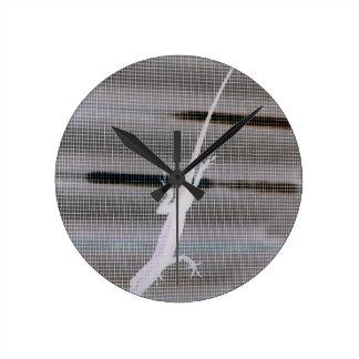 Negative image of a lizard on a window screen round clock
