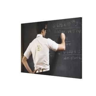 Nerdy man writing on blackboard canvas print