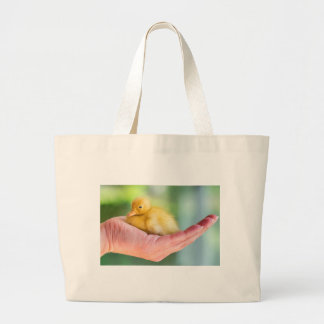 Newborn yellow duckling sitting on hand large tote bag