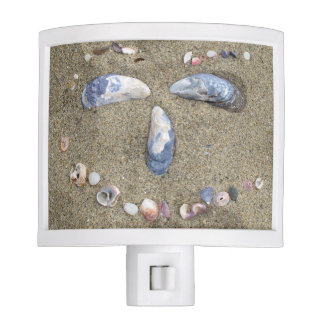 Night light face made in sand with sea shells