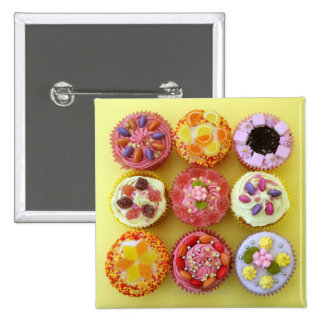 Nine cupcakes each decorated with candy in a 2 inch square button