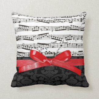 Notes de musique et ruban de rouge de faux coussin décoratif