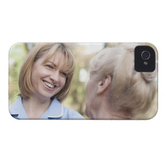 Nurse smiling and talking to a senior woman iPhone 4 covers