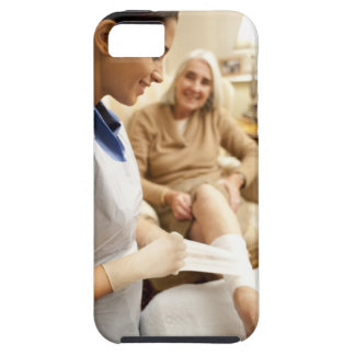 Nurse wrapping bandage on senior woman's leg to iPhone 5 cover