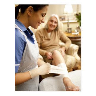 Nurse wrapping bandage on senior woman's leg to postcard