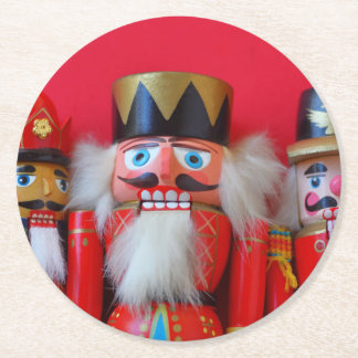 Nutcrackers in red uniforms round paper coaster