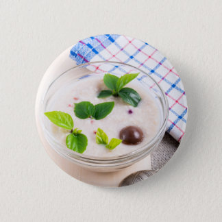 Oatmeal in a bowl of glass with chocolate candy 2 inch round button