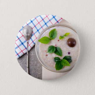 Oatmeal with chocolate candy and a silver spoon 2 inch round button