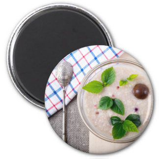 Oatmeal with chocolate candy and a silver spoon 2 inch round magnet