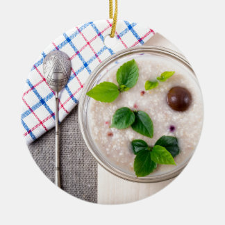 Oatmeal with chocolate candy and a silver spoon round ceramic ornament