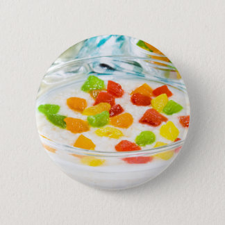 Oatmeal with colorful candied fruits in a glass 2 inch round button