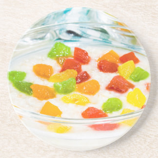 Oatmeal with colorful candied fruits in a glass coaster