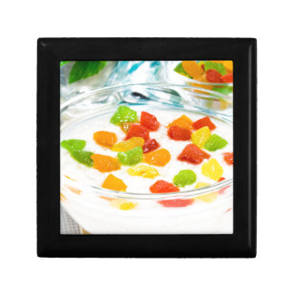 Oatmeal with colorful candied fruits in a glass gift box