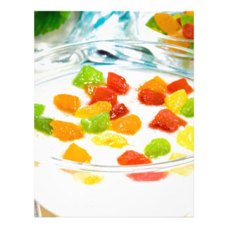 Oatmeal with colorful candied fruits in a glass letterhead