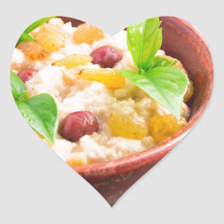 Oatmeal with raisins and berries in a wooden bowl heart sticker