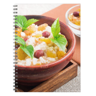 Oatmeal with raisins and berries in a wooden bowl notebooks