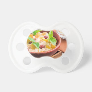 Oatmeal with raisins and berries in a wooden bowl pacifier
