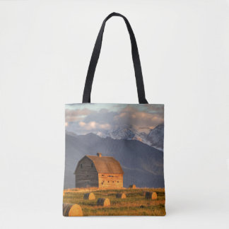 Old barn framed by hay bales and dramatic tote bag