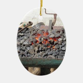 Old-fashioned blacksmith furnace . Burning coals Ceramic Oval Ornament