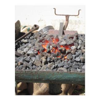 Old-fashioned blacksmith furnace . Burning coals Letterhead