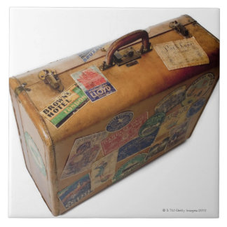old fashioned suitcase with travel stickers tile