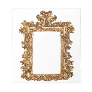 Old gold frame isolates on white notepad