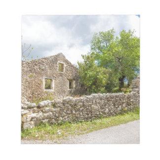 Old historic house as ruins along road notepad