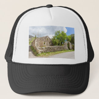 Old historic house as ruins along road trucker hat