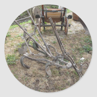 Old iron plow and other agricultural tools classic round sticker