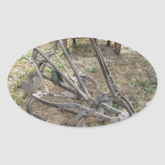 Old iron plow and other agricultural tools oval sticker