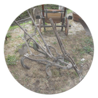 Old iron plow and other agricultural tools plate