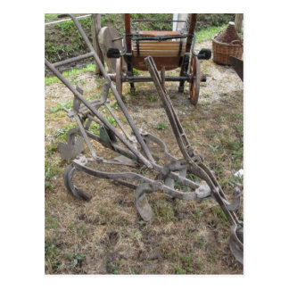 Old iron plow and other agricultural tools postcard