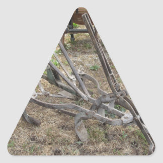 Old iron plow and other agricultural tools triangle sticker
