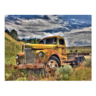 Old truck abandoned in field postcard
