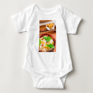 Old wooden bowl of healthy oatmeal with berries baby bodysuit