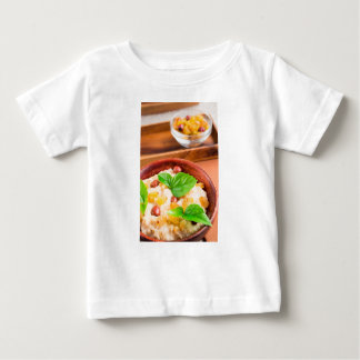 Old wooden bowl of healthy oatmeal with berries baby T-Shirt