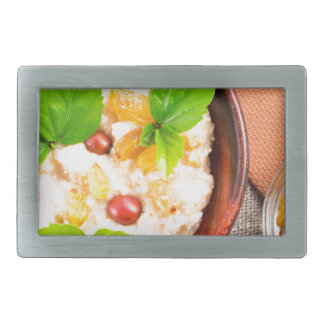 Old wooden bowl of healthy oatmeal with berries belt buckles