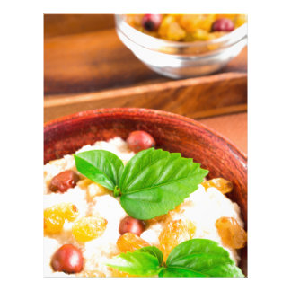 Old wooden bowl of healthy oatmeal with berries letterhead